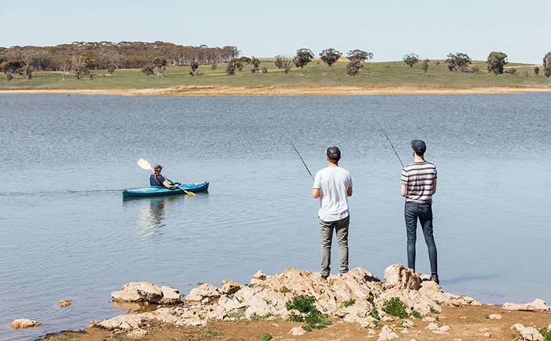 Two men fishing and a woman kayaking at Bundaleer Reservoir